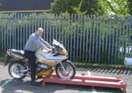 Roll the bike onto a purpose made stillage